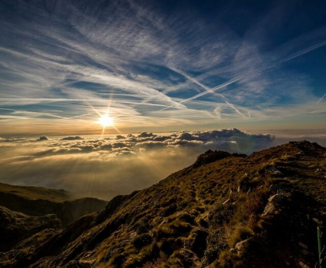 Pushing through the clouds, dazzled by the sun sitting on top. #sky #mountains