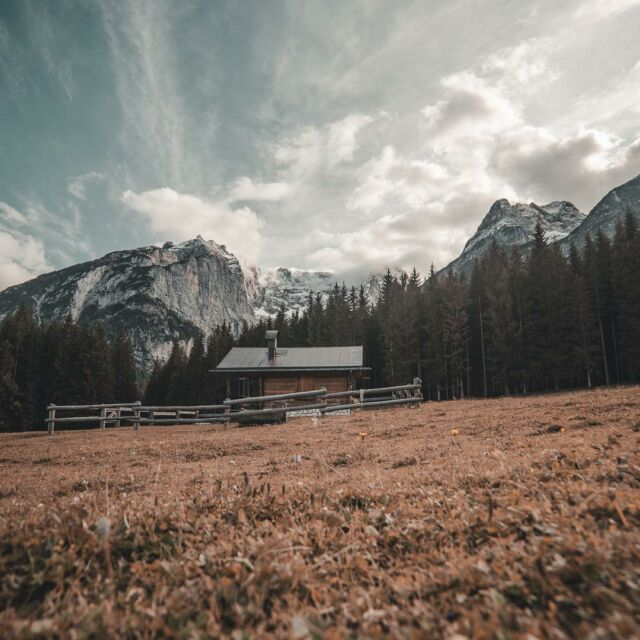 A lonely cabin hides at the foot of the range, hoping to go unnoticed. #mountains #wild